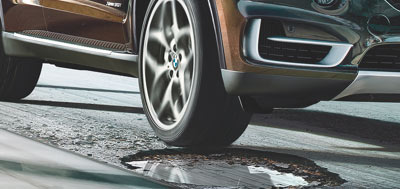 BMW vehicle driving over a pothole in the road